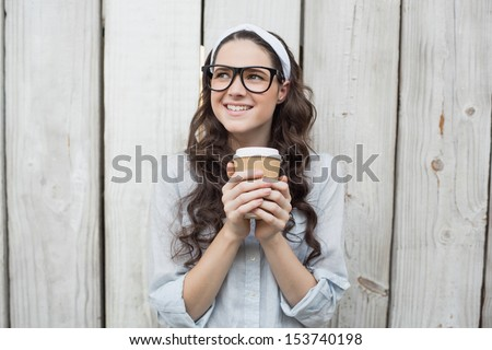 Pensive trendy woman with stylish glasses holding coffee posing on wooden background - stock photo