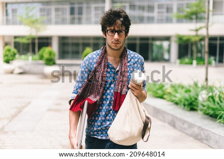 Pensive university student with bag and laptop walking on campus - stock photo