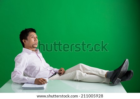 Pensive Vietnamese businessman relaxing on the chair with his feet on the table - stock photo