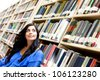 Pensive woman at the library surrounded by books - stock photo