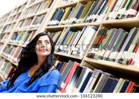 Pensive woman at the library surrounded by books
