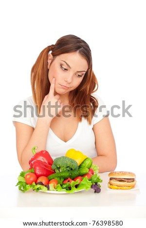 pensive woman choosing burger or vegetables. isolated on white background - stock photo