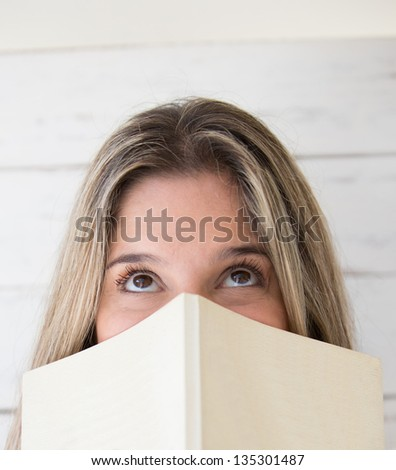 Pensive woman holding a book and looking up