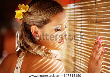 pensive woman in the light of tropical sun on a vacation (soft focus on her eyes and lashes) - stock photo