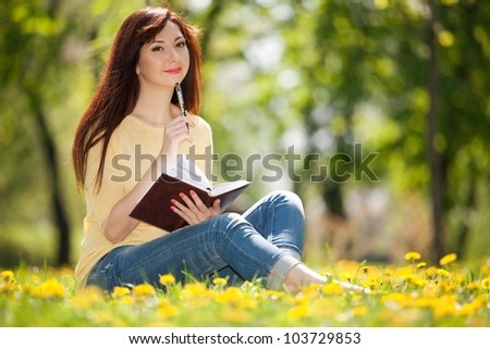 Pensive woman in the park with flowers