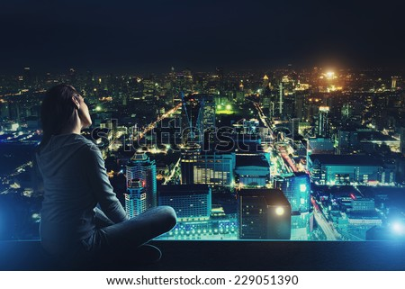 Pensive woman is looking at night city - stock photo