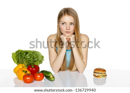 Pensive woman making decision between healthy food and fast food, over white background - stock photo