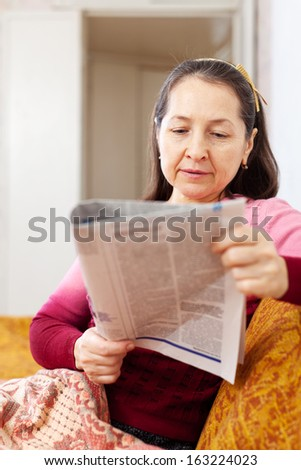 pensive woman reading newspaper on sofa at home