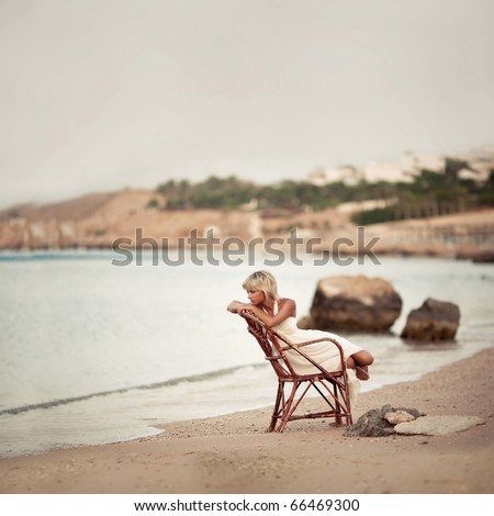 pensive woman sitting on the dunes watching the sea - stock photo