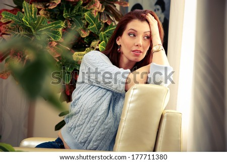Pensive woman sitting on the sofa and looking in window at home - stock photo