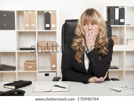 Pensive worried businesswoman biting her nails and looking off to the side with a serious thoughtful expression as she anticipates trouble - stock photo