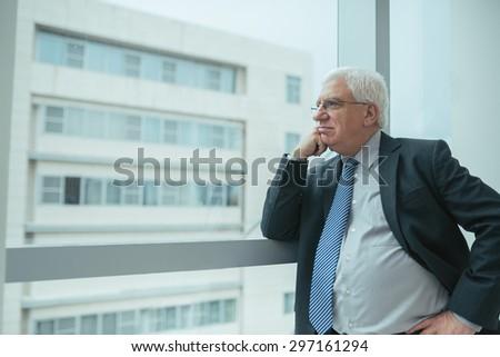 Pensive worried senior businessman looking through the office window - stock photo