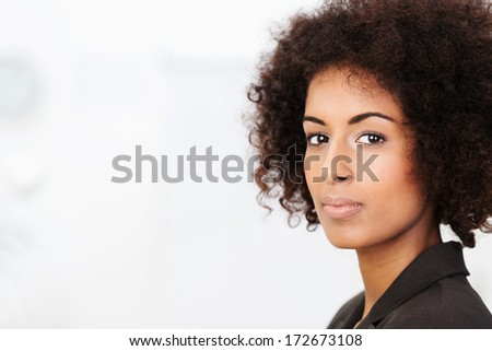 Pensive young African American woman standing looking sideways at the camera with a serious contemplative look over white with copyspace