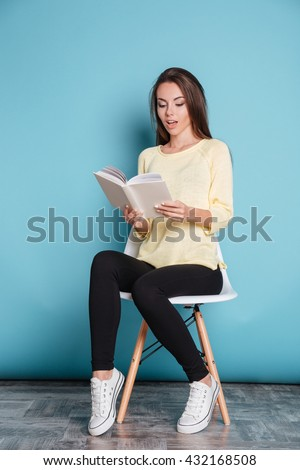Pensive young attractive girl reading book and sitting on chair isolated on the blue background - stock photo