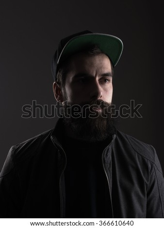 Pensive young bearded man wearing baseball cap looking away. Low key dark shadow portrait over black background. - stock photo