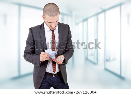pensive young business man with money, at the office - stock photo