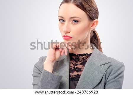Pensive young business woman touching her face, isolated on gray - stock photo