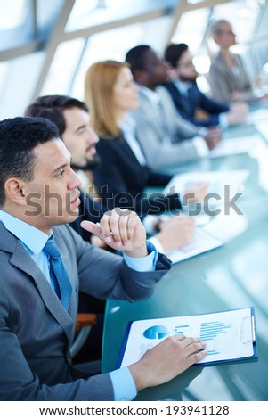 Pensive young businessman listening to explanations at seminar on background of other listeners - stock photo