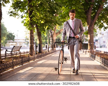 Pensive young businessman walking with bicycle on the street in town  - stock photo