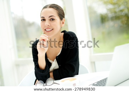 Pensive young businesswoman looking at the camera with a smile and thoughtful expression as she sits at a table in a bright sunny room with her laptop computer - stock photo