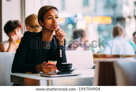 Pensive young businesswoman using smartphone in coffee shop - stock photo