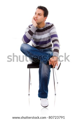 Pensive young casual man on a chair, isolated on white - stock photo