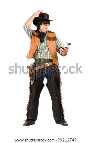Pensive young cowboy with a bottle of whiskey in hand - stock photo