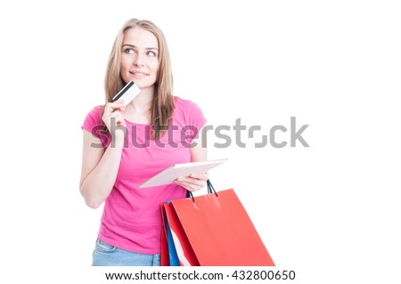 Pensive young customer with credit card and tablet in her hand as online shopping payment concept isolated on white with copy space