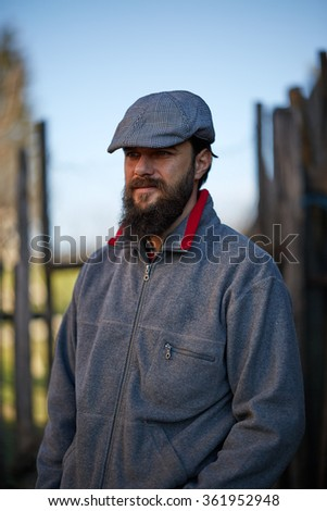 Pensive young farmer standing in the courtyard - stock photo