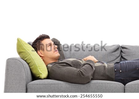 Pensive young guy laying on a sofa isolated on white - stock photo