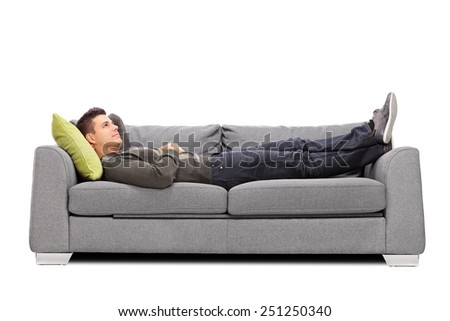 Pensive young guy laying on a sofa isolated on white background - stock photo