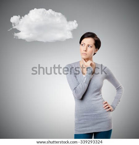 Pensive young lady touches her neck, isolated on grey background - stock photo