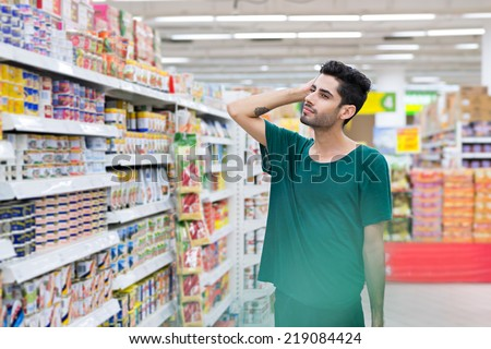 Pensive young man choosing food in the supermarket - stock photo