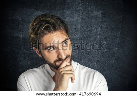 Pensive young man looks at copy space - stock photo