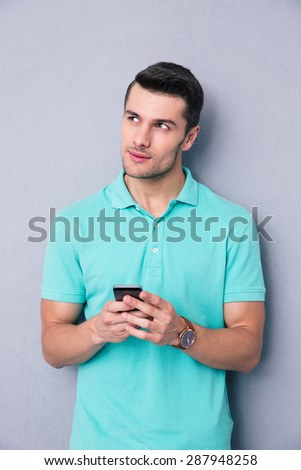 Pensive young man using smartphone over gray background - stock photo