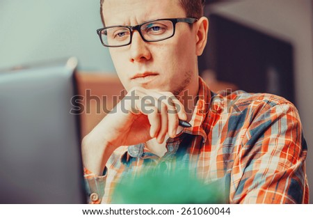 Pensive young man working over laptop in the office - stock photo