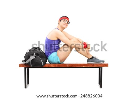 Pensive young sportsman sitting on a bench isolated on white background - stock photo