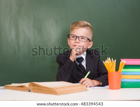 Pensive young student in black suit near empty green chalkboard.