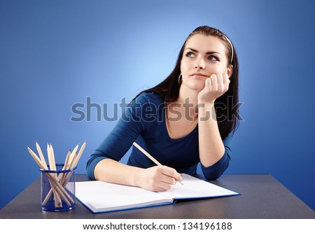 Pensive young student sitting at her desk with her notebook in front, in closeup pose, on blue background