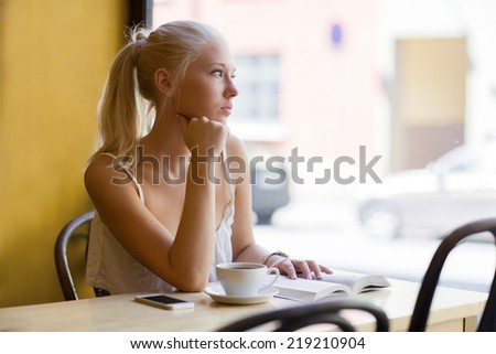Pensive young woman at cafe looks out the window - stock photo