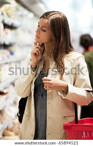 Pensive young woman at supermarket
