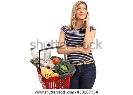 Pensive young woman holding a shopping basket isolated on white background - stock photo