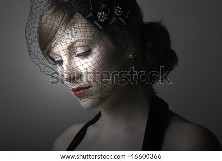 pensive young woman in a veil looks down
