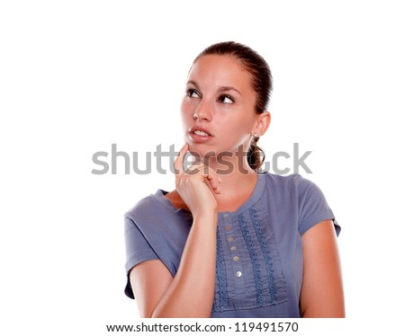 Pensive young woman looking to her right up on blue shirt against white background - copyspace - stock photo