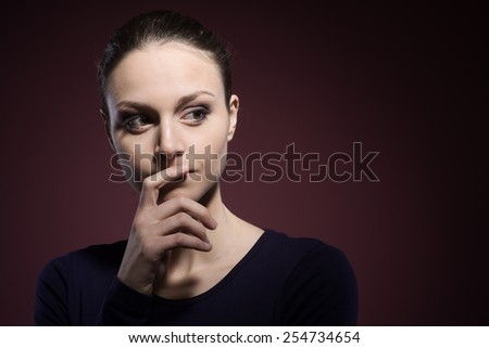 Pensive young woman posing with hand on chin - stock photo