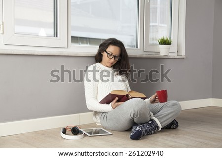Pensive young woman reading a book while sitting on the floor at home. - stock photo
