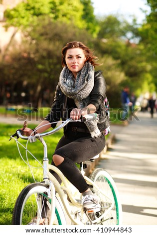 Pensive young woman riding a bicycle in the green city park