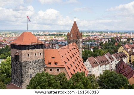 Pentagonal tower, with the Imperial Stables and Luginsland behind it, at Kaiserburg Imperial Castle in Nuremberg, Franconia, Bavaria, Germany. Nuremberg city in the background. - stock photo
