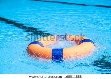 Peolple throw Life ring floating to someone in the pool - stock photo