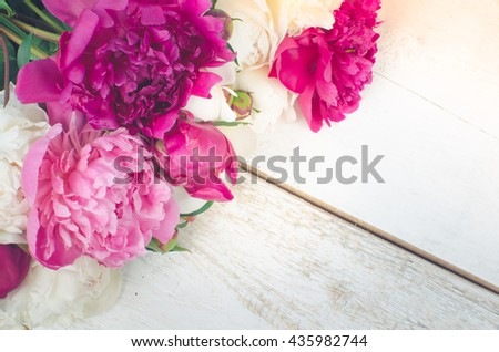 Peony background. Fuchsia, pink and white peonies on white wooden table with place for text. Spring flowers peonies. Happy Mothers Day. Mother's Day greetings card. Mothers Day gift. Copy space. - stock photo